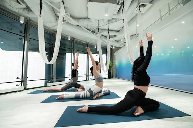 Levantando as mãos. duas mulheres ativas e em forma e um homem levantando as mãos enquanto fazem ioga juntos