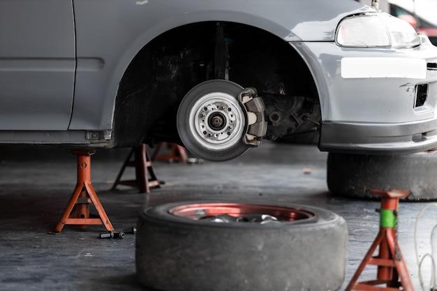 Levantando um carro para trocar de pneu na garagem.