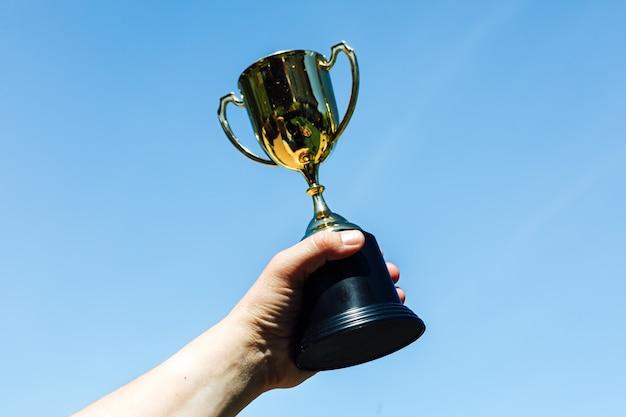 Levante a mão de uma taça de campeão, com o céu ao fundo. conceito de vitória