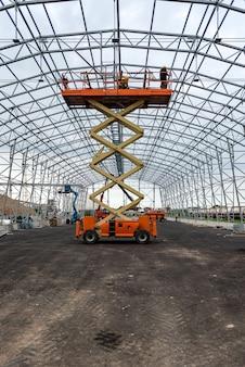 Levante com trabalho de plataforma no campo de construção do hangar de armazém.