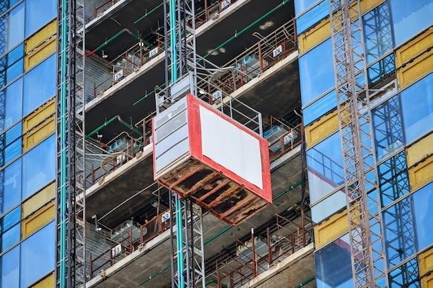 Levante em um arranha-céu de vidro em construção