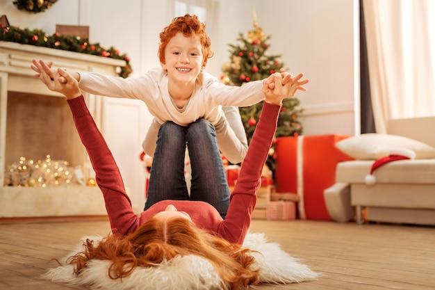 Levante-me mais alto. madura atenta e seu filho adorável passando um tempo juntos e fingindo voar enquanto se divertem em casa.