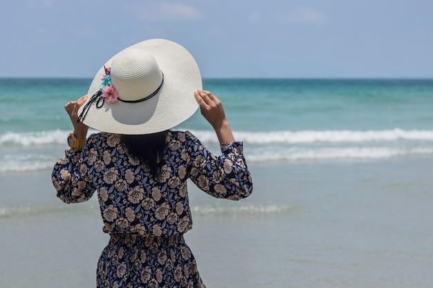 Levante-se a vista traseira da menina que veste um chapéu para relaxar fora da praia e olhar a opinião do mar em sattaheeb, tailândia.