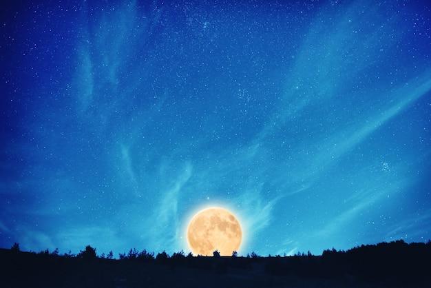 Levante-se na lua cheia à noite no céu azul escuro com muitas estrelas e nuvens