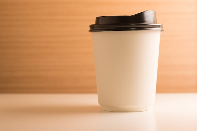 Levar a xícara de café de papel no fundo de madeira mesa branca