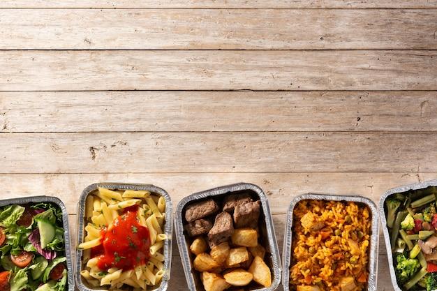 Leve alimentos saudáveis em caixas de papel alumínio na mesa de madeira