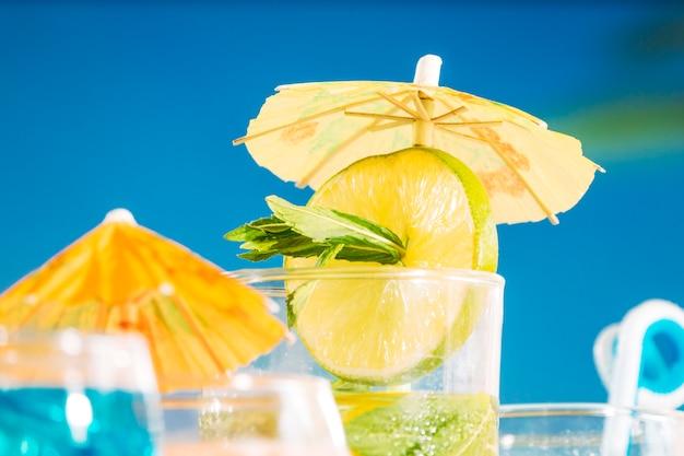 Leve, bebida, com, cortado, lima, e, hortelã, em, guarda-chuva, decorado, vidro