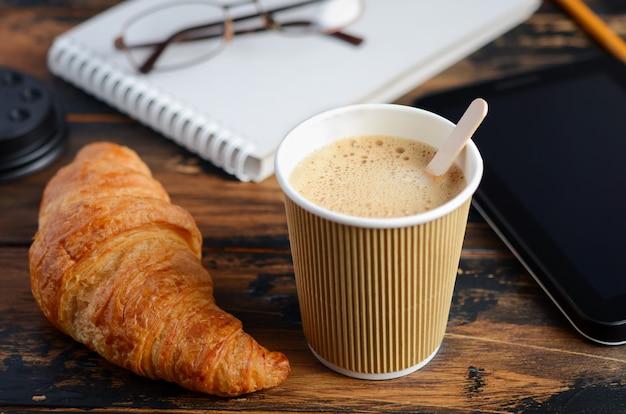 Leve embora o copo de café com o croissant na tabela de madeira.