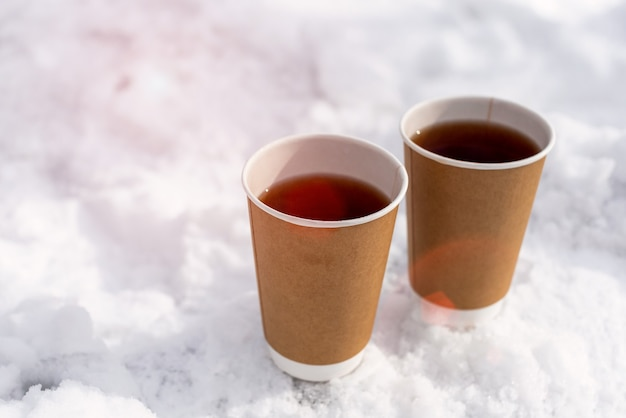 Leve o copo de papel artesanal com chá contra a luz do sol na neve no inverno. conceito de bebida quente de rua. copie o espaço.