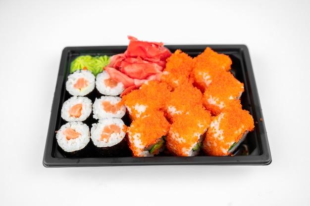 Leve os rolos de sushi em um recipiente de plástico, califórnia, rolo de maki de salmão, gengibre rosa, wasabi. conceito de entrega de sushi