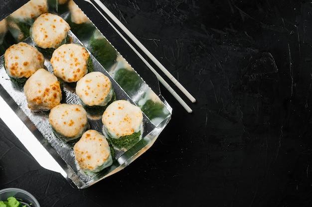 Leve rolinhos de sushi em recipientes, rolinhos da filadélfia e rolinhos de camarão assados colocados em uma mesa de pedra preta