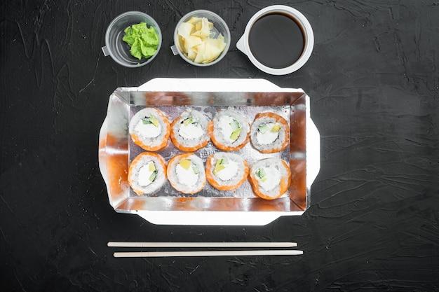 Leve rolinhos de sushi em recipientes, rolinhos da filadélfia e rolinhos de camarão assados em pedra preta