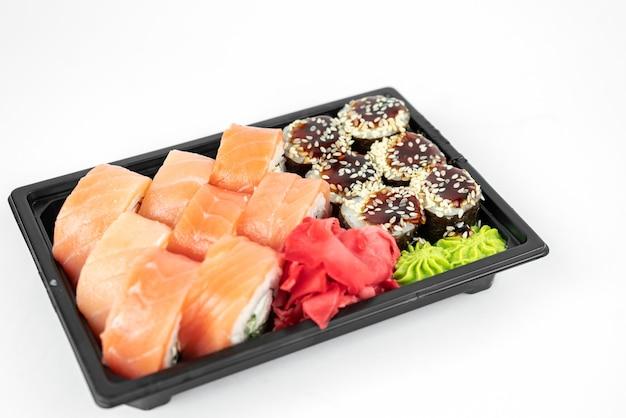 Leve sushi em recipientes de plástico, rolos da filadélfia e unagi maki, molho de soja, gengibre rosa, wasabi, conceito de entrega de sushi