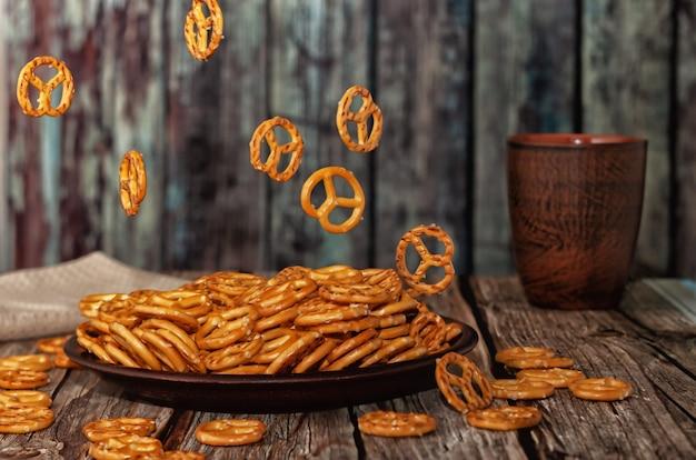 Levitação de alimentos. pequenos biscoitos em forma de pretzels caindo em uma tigela de barro, fundo de madeira.
