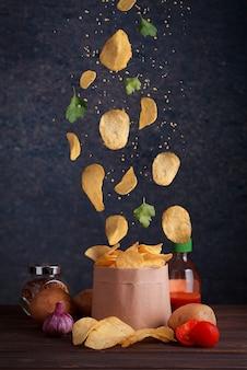 Levitando batatas fritas. chips caem em uma sacola artesanal com batatas e tomates na mesa de madeira