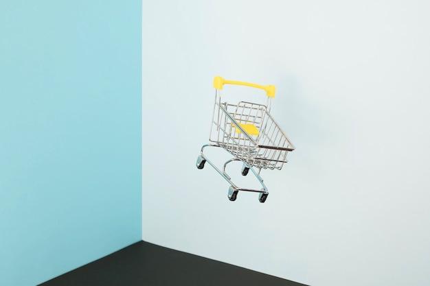 Levitando carrinho de compras em fundo azul