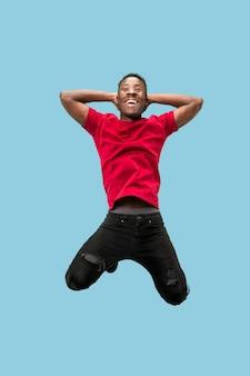 Liberdade de movimento e movimento para frente. o feliz surpreso jovem africano pulando um contra o fundo azul do estúdio. homem correndo em movimento ou movimento. emoções humanas e expressões faciais