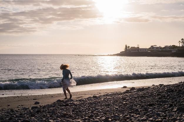 Liberdade e boa mulher dançam e se divertem na praia na costa aproveitando o verão e o pôr do sol. atividade de lazer ao ar livre para bela senhora descalça brincando com as ondas