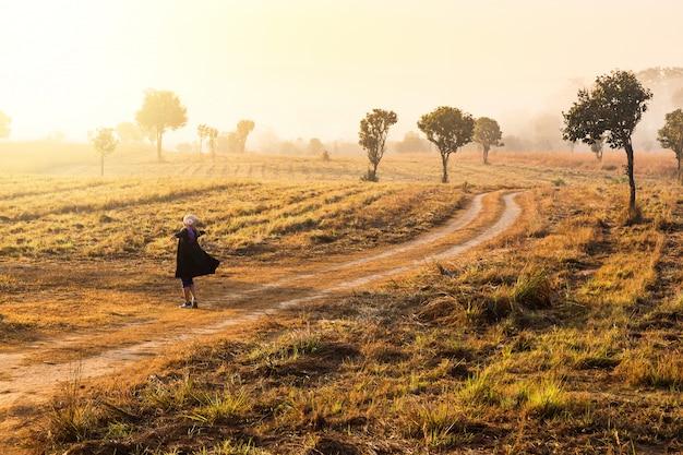 Liberdade e sentir-se bem conceito mulher levantando as mãos no fundo do nascer do sol no caminho da estrada