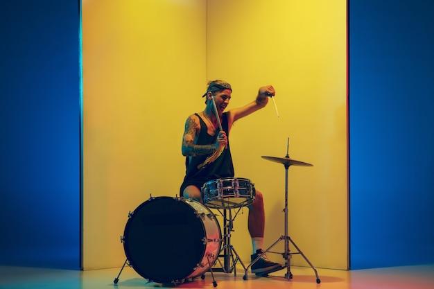 Liberdade. jovem músico com bateria tocando em fundo amarelo em luz de néon. conceito de música, hobby, festival, entretenimento, emoções. baterista alegre e inspirado. retrato colorido do artista.