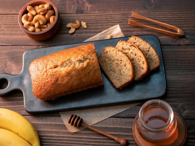 Libra caseiro do pão de banana cortada com porcas e mel de caju na tabela de madeira.