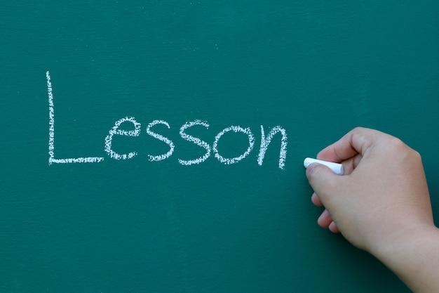 Lição de tópico de escrita à mão com giz branco no quadro-negro