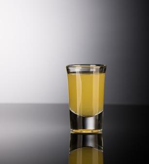 Licor alcoólico amarelo em um copo isolado em um fundo escuro com luz de fundo