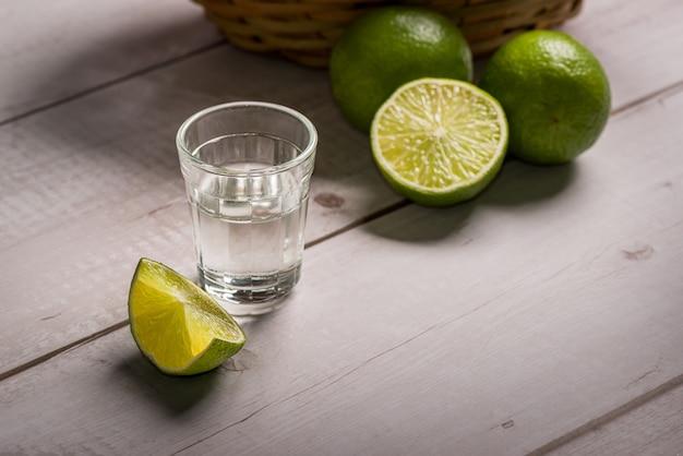 Licor de cana-de-açúcar em um pequeno copo sobre uma mesa de madeira com limões