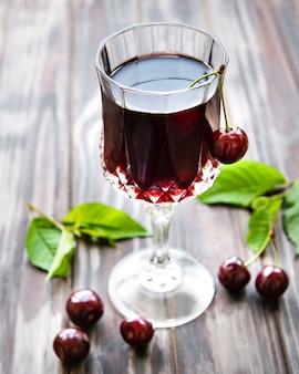 Licor de cereja em um copo e frutas frescas em uma mesa de madeira