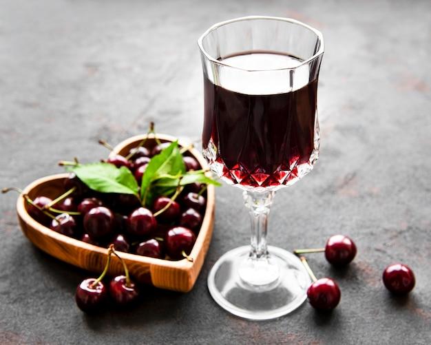 Licor de cereja em um copo e frutas frescas em uma superfície de concreto preto