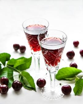 Licor de cereja em um copo e frutas frescas em uma superfície de mármore branco