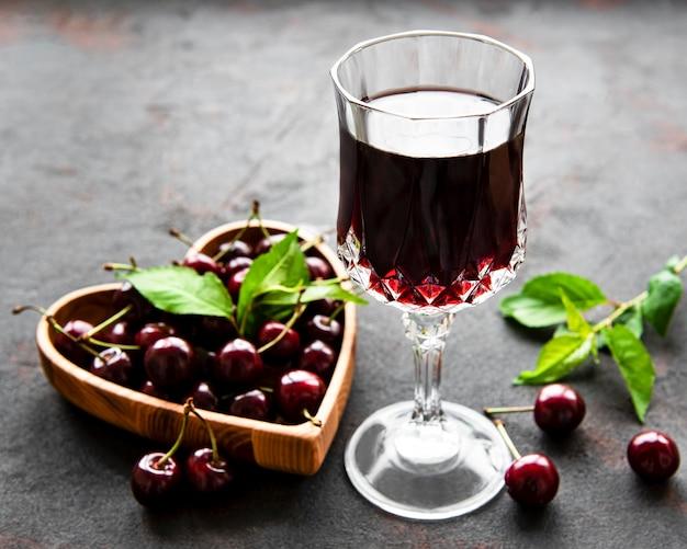 Licor de cereja na taça e frutas frescas