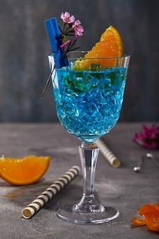 Licor de curaçao azul com laranja e flor para o projeto em uma mesa cinza