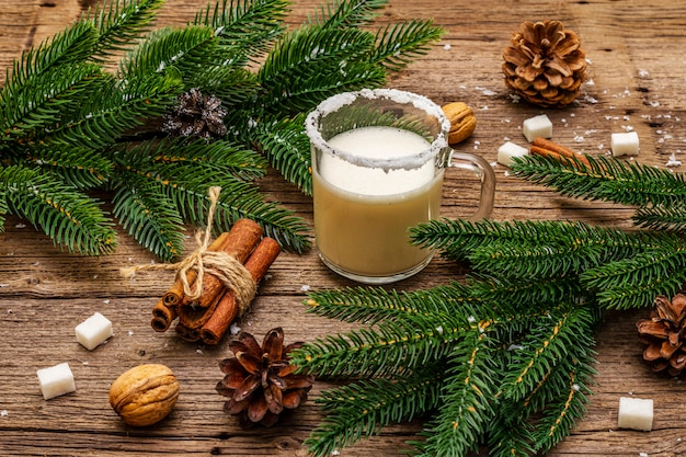 Licor de gemada de natal ou coquetel de cola mono. bebida clássica de inverno na caneca de vidro, decorações de natal. ramos verdes, canela, nozes, açúcar.