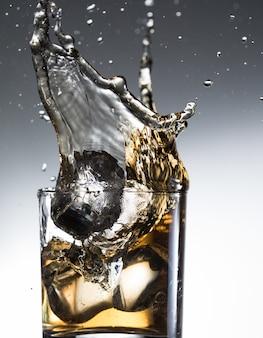 Licor de uísque cocktail respingo álcool em vidro