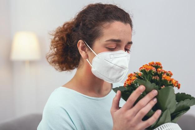 Lidar com alergias. jovem com aparência doente usando uma máscara respiratória de proteção que a mantém protegida de uma flor que causa suas alergias sazonais
