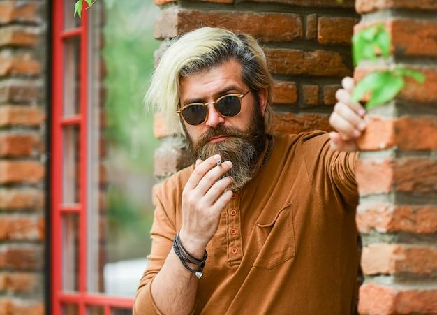 Lide com o estresse. homem hippie punk fumando. tabagismo e hábito. fumo passivo ou passivo. homem caucasiano brutal em copos. homem que fuma ao ar livre. cigarro de fumo na moda homem maduro.