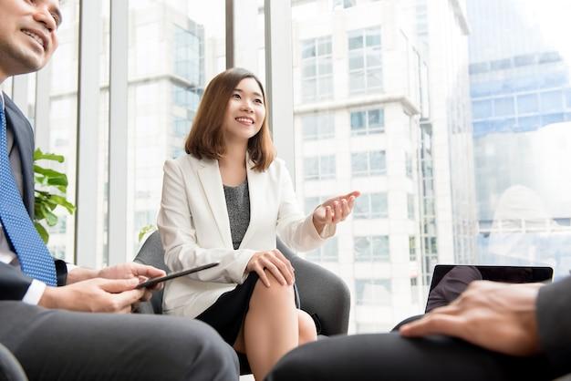 Líder asiático da mulher de negócios em uma reunião que discute o trabalho
