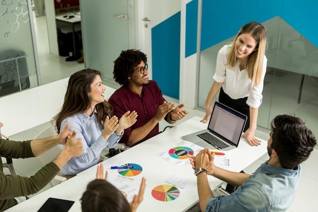 Líder da equipe feminina muito falando com grupo de raça mista de pessoas no escritório