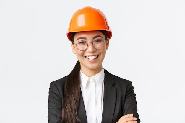 Líder da equipe sorridente, engenheira-chefe asiática no capacete de segurança e no terno cruza os braços, confiante, sorrindo feliz, apresenta a empresa, parede branca de pé.