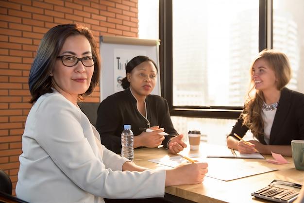 Líder de empresária sênior asiática na sala de reunião