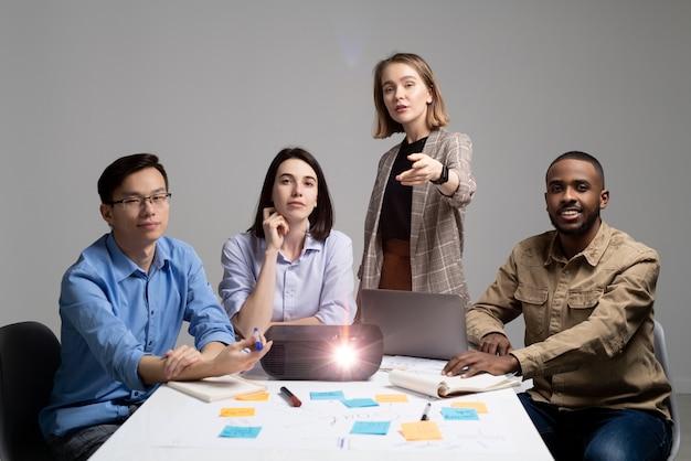 Líder de equipe apontando para a câmera enquanto o convida para fazer parte da equipe de inicialização, grupo de especialistas sentados à mesa com projetor