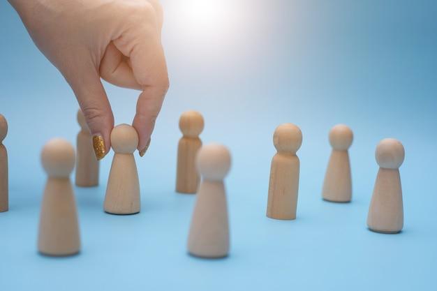 Líder de equipe de sucesso, a mão de uma mulher escolhe as pessoas que se destacam umas das outras.