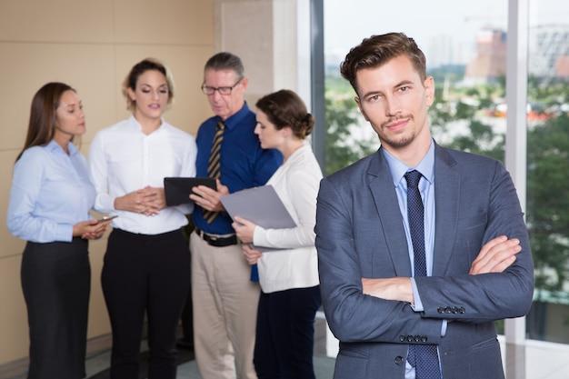 Líder de negócio confiável com a equipe no fundo