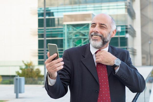 Líder de negócio maduro positivo feliz que ajusta o laço