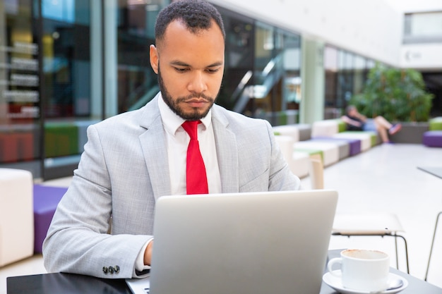 Líder de negócios bonito confiante usando laptop