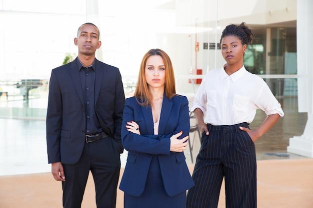 Líder de negócios de senhora e sua equipe olhando para a câmera