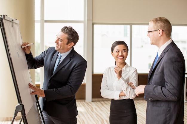 Líder de negócios, desenho no flipchart na briefing
