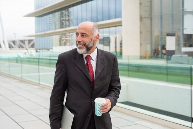 Líder de negócios maduro positivo feliz desfrutando de café