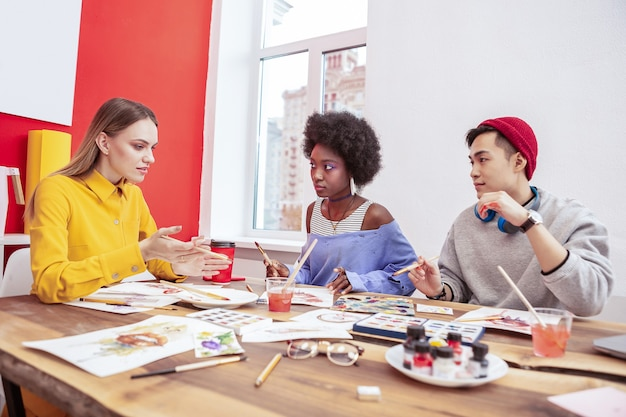 Lider do time. dois talentosos trainees criativos de revista de moda ouvindo o líder de sua equipe